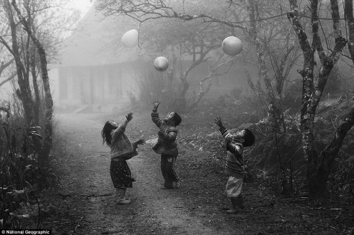 Vo Anh Kiet H'Mong minority children were playing with their balloons on the foggy day in Moc Chau - Ha Giang province Viet Nam in January 2012.