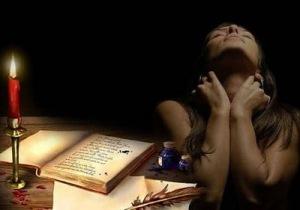 mujer+sola+trsite+preocupada+escribiendo+libro+vela+
